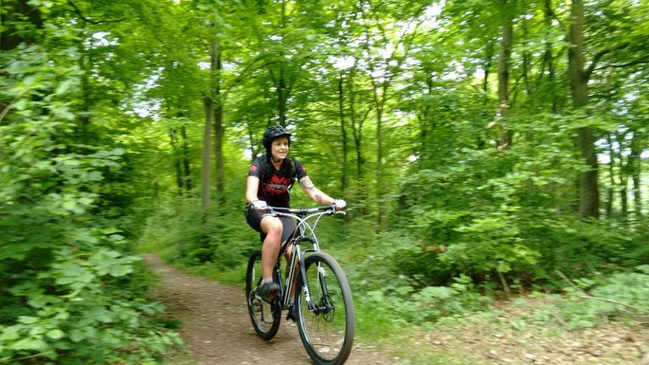 image of woman riding mountain bike - looking happy