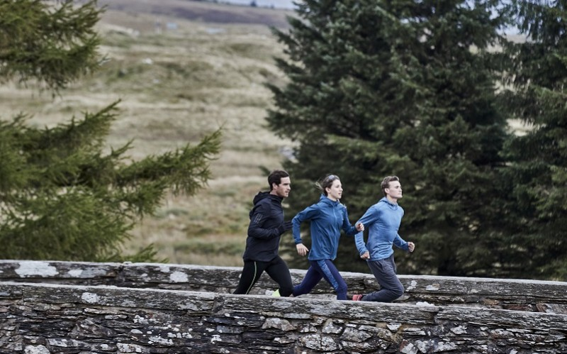 Three runners on a bridge in winter