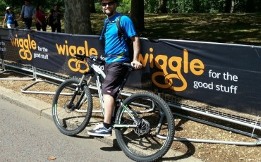 Andy on his bike in front of a Wiggle banner