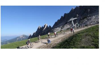 A group of cyclists riding up a steep path in a mountainous environment