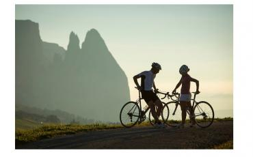 two cyclists talking, mountains in background